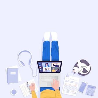 Trabalhe em casa conceito. vista superior do jovem sentado no chão e usando o laptop para videoconferência em casa.