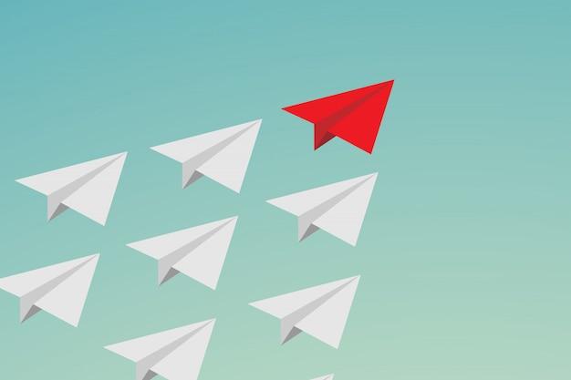 Trabalho em equipe de liderança plana e coragem. avião de papel vermelho e muitos brancos no céu