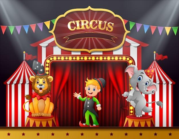 Treinador de circo com elefante e leão no palco