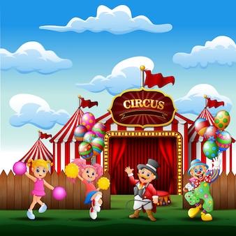 Treinador de desenho animado, palhaço com as líderes de torcida na entrada do circo