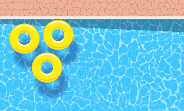 Três anéis de piscina amarelos flutuando em uma piscina