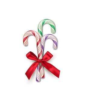 Três bastões de doces listrados de cores diferentes com um laço vermelho isolado no fundo branco