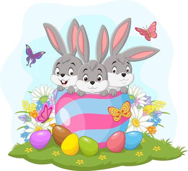 Três coelhinhos da páscoa no ovo de páscoa