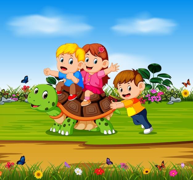 Três crianças estão brincando na grande tartaruga na floresta