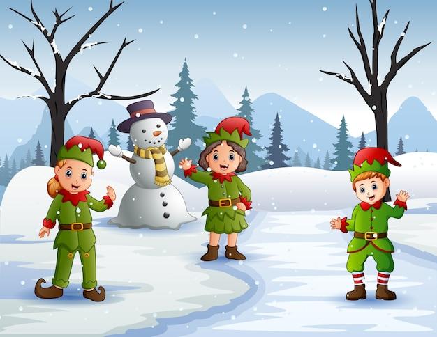 Três elfos acenando na floresta de neve