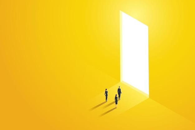 Três empresários pararam em frente a uma porta enorme brilhando com a luz