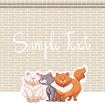 Três gatos e parede de tijolo
