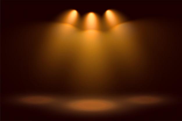 Três holofotes dourados e fundo de palco
