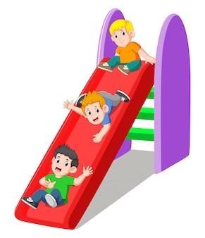 Três menino brincando no slide