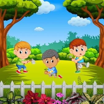 Três meninos aprendendo jardinagem ao ar livre