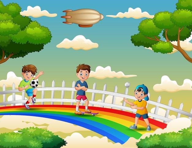 Três meninos felizes desempenham atividades diferentes sobre o arco-íris