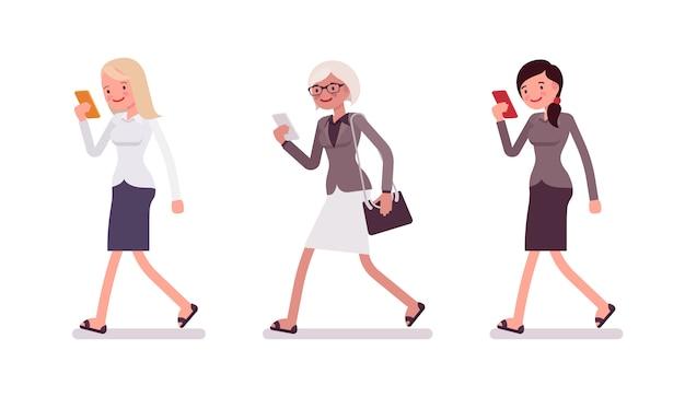 Três mulheres, andar, segurando, um, smartphone