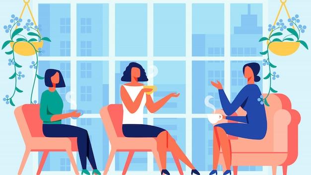Três mulheres se comunicam perto da janela panorâmica.