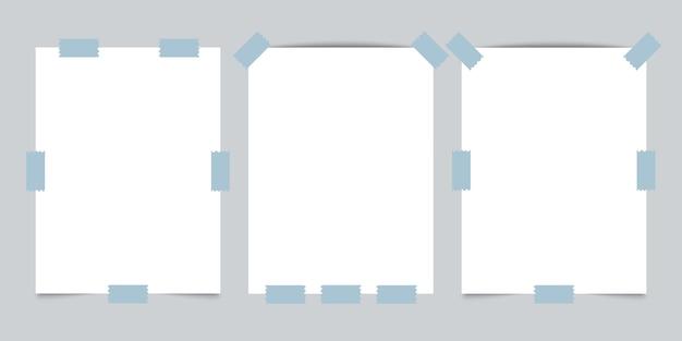 Três papéis vazios com fita adesiva em fundo cinza.