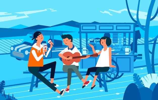 Três pessoas andando na barraca de comida de rua enquanto toca guitarra