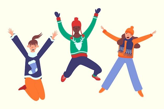Três pessoas vestindo roupas de inverno pulando