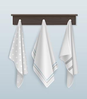 Três toalhas limpas de algodão ou linho brancas e bolinhas penduradas em um gancho de madeira marrom na parede azul