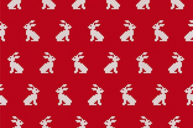 Tricotar o fundo sem costura com coelhos. padrão de vermelho de natal. ilustração vetorial.