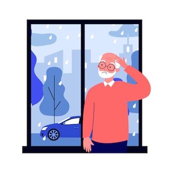 Triste homem sênior em pé perto da janela e olhando para a chuva