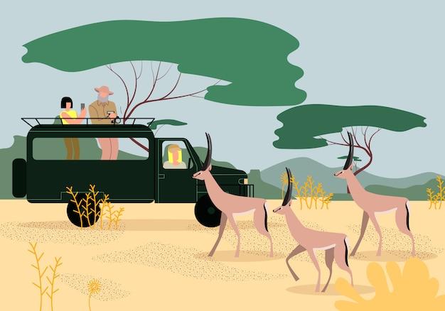 Turistas que conduzem o jipe no safari em áfrica. savana