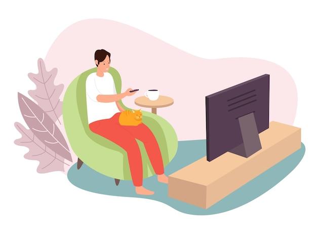 Um adolescente está assistindo televisão com o gato e uma xícara de café na mesa