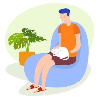Um adolescente está brincando com um gato de estimação, sentado no sofá