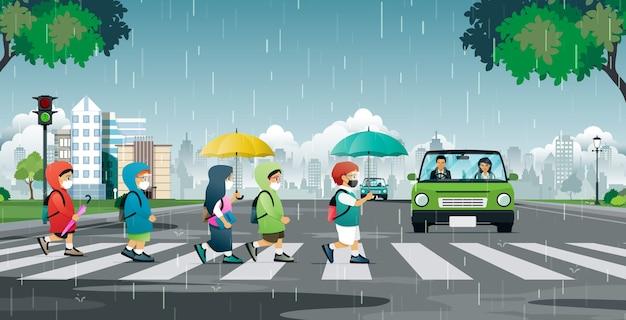 Um aluno usando máscara está atravessando a rua na chuva.