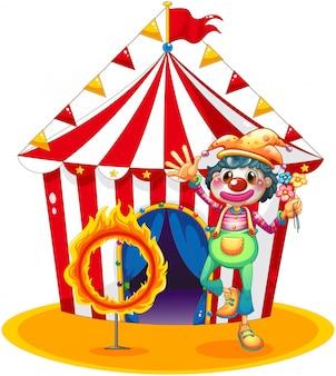 Um anel de fogo e um palhaço na frente de uma tenda de circo