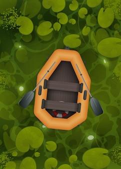 Um barco de borracha laranja flutua por um pântano com folhas de nenúfar, vista de cima.