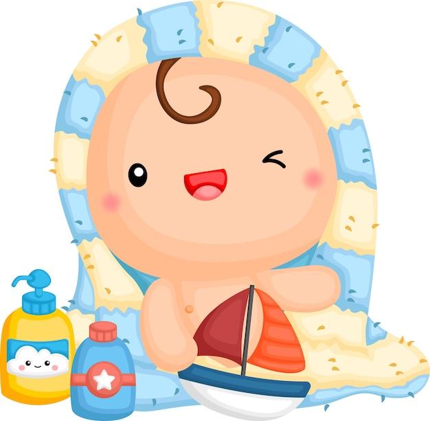 Um bebê enrolado em uma toalha segurando um brinquedo