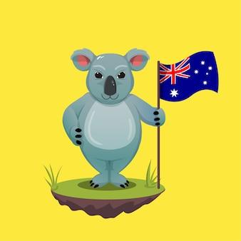 Um coala australiano em pé na grama verde segurando uma bandeira australiana. comemorando feliz dia da austrália