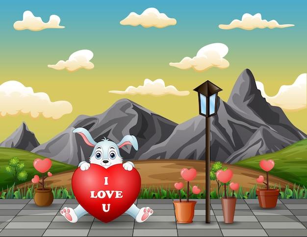 Um coelho segurando um coração vermelho na paisagem do parque