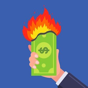 Um dólar está queimando em uma mão. ilustração plana.