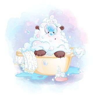 Um filhote de urso pequeno em espuma e sabão senta-se em uma banheira e olha para uma bolha de sabão no nariz.
