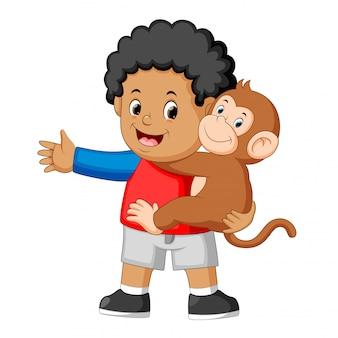 Um garotinho segurando um macaco engraçado