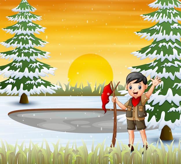 Um garoto escoteiro com bandeira vermelha na paisagem de inverno