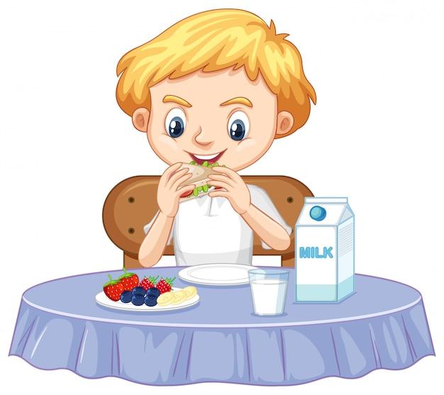 Um garoto feliz tomando café da manhã