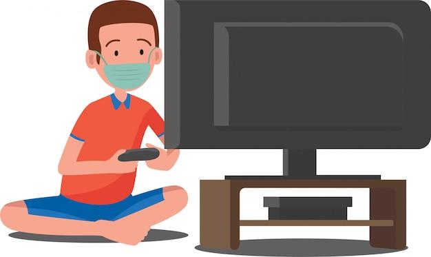Um garoto jogando videogame enquanto está sentado no chão usando máscara facial