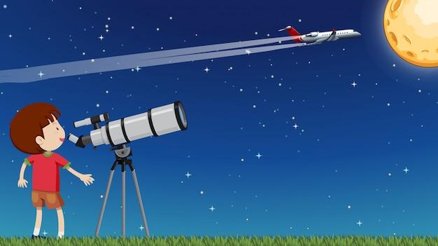 Um garoto olhando a lua com telescópio