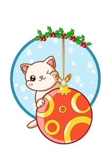 Um gato fofo na bola de natal com folhas de azevinho