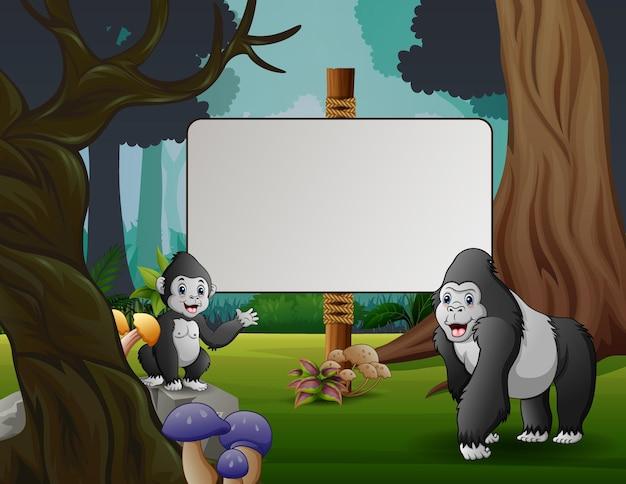 Um gorila fofo com seu filhote parado perto da placa em branco