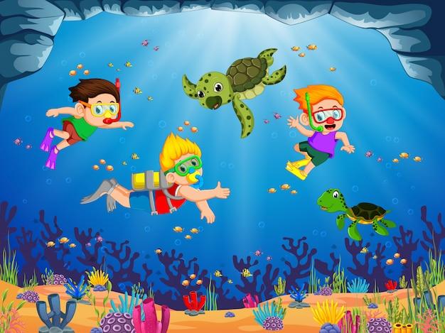 Um grupo de crianças está brincando e mergulhando com a tartaruga verde