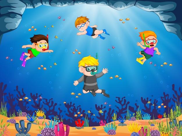 Um grupo de crianças está mergulhando sob o mar azul com seu amigo
