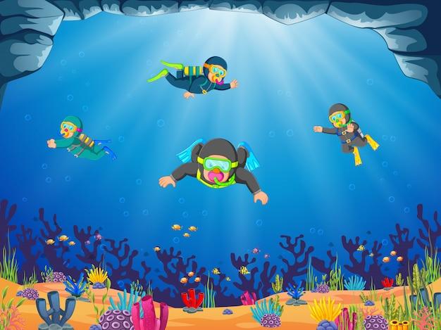 Um grupo de um mergulhador profissional está mergulhando sob o mar azul