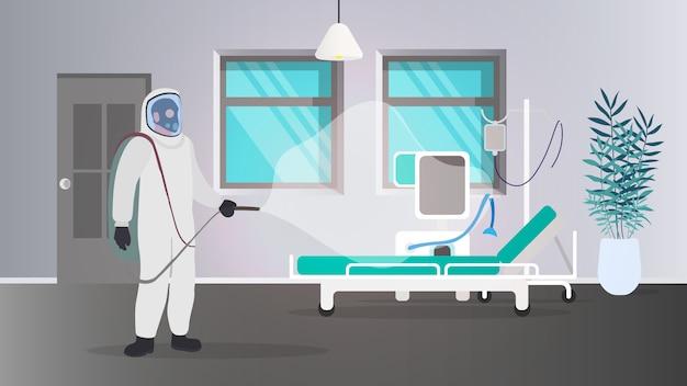 Um homem em um traje de proteção branco desinfeta um quarto de hospital. hospital, um homem em um traje de proteção.