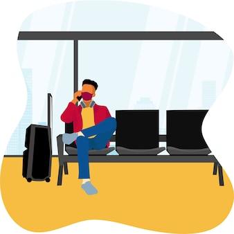 Um homem esperando o avião na sala de espera do aeroporto
