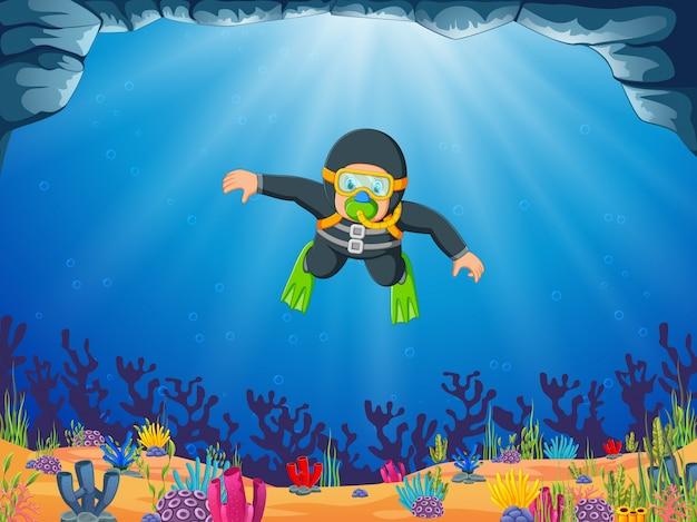 Um homem está mergulhando sob o mar azul com os óculos de natação amarelos