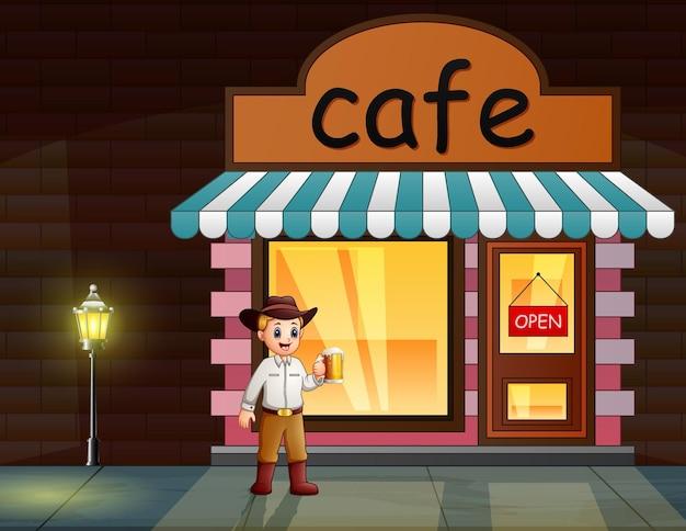 Um homem segurando um copo de bebida em frente ao café