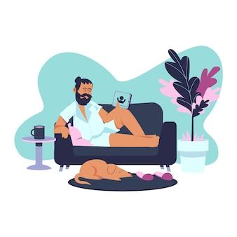Um homem segurando um tablet relaxando em casa no sofá