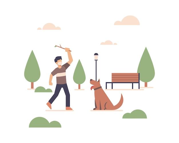 Um homem usando uma máscara facial e brincando com seu cachorro em um parque público em espaço aberto.